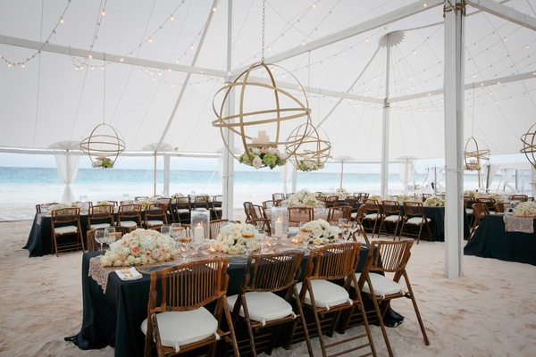 Tent wedding reception on sand navy blue and light pink wedding decor wood chairs and gold orbs