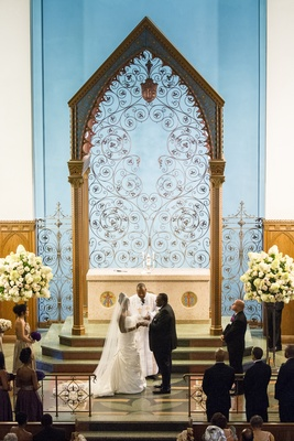 African American bride and groom at altar with pastor
