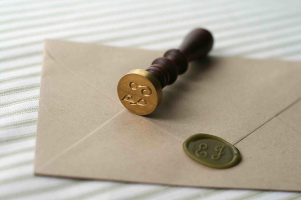 Custom wax seal stamp with dark wood handle and gold stamper