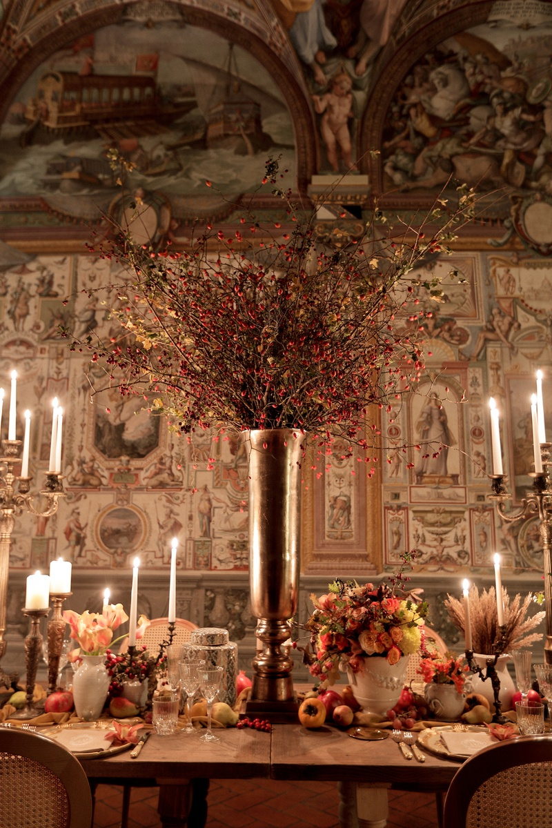 renaissance inspired tablescape in palace in florence, large silver vase, red blossoming branches