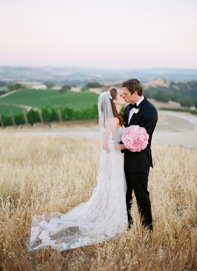 Bride and groom kissing at family vineyard