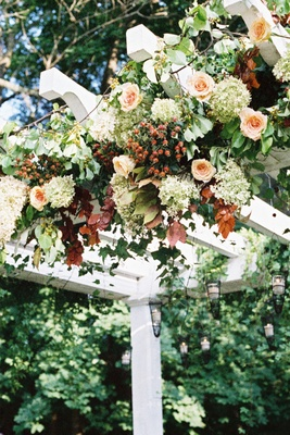 White garden ceremony structure with orange roses and white flowers