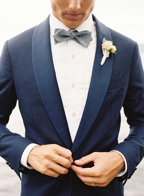 Groom buttoning up navy blue tuxedo jacket with grey bow tie white shirt ivory flower boutonniere