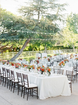 Long family wedding table with low flower arrangements and white linens