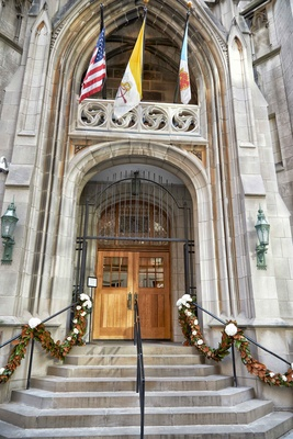 Wedding venue in Chicago St. James Chapel with magnolia leaf garlands on stair hand rail flags