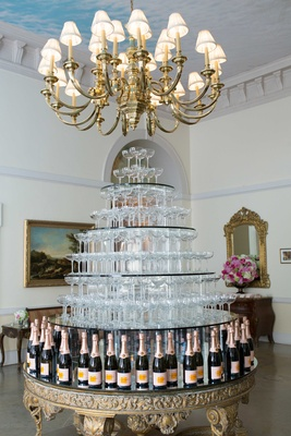 Gold ornate table with champagne bottles holding up tiers of coupe champagne glasses in tower