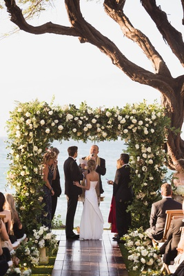 maui destination wedding,lush chuppah with heavy greenery and white roses