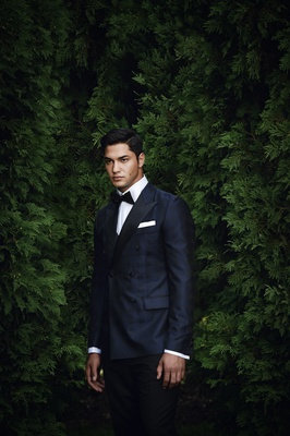 groom in midnight blue tuxedo with black bow tie