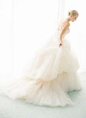 Bride holding wedding dress skirt for portrait