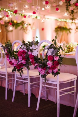 Bride and groom chairs at head table with greenery garland pink red white flowers