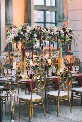 gold pillars with flowers across burgundy white ivory blush