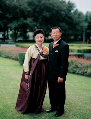 Mother in traditional Korean dress and father in a black tuxedo