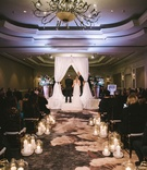 candlelit aisle leading to white drapery chuppah and light blue lighting
