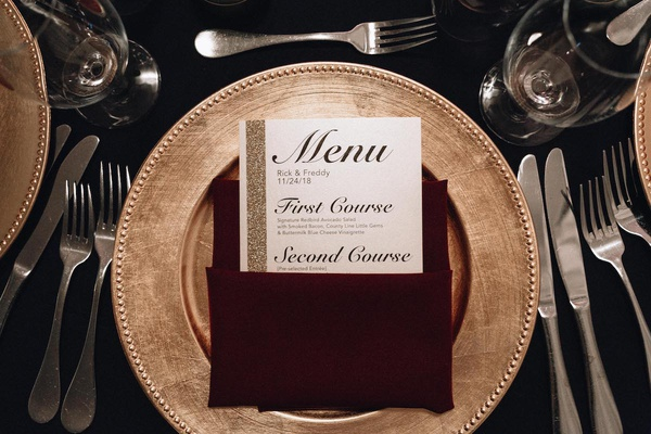 wedding reception menu with gold glitter border on side placed in burgundy napkin on gold charger