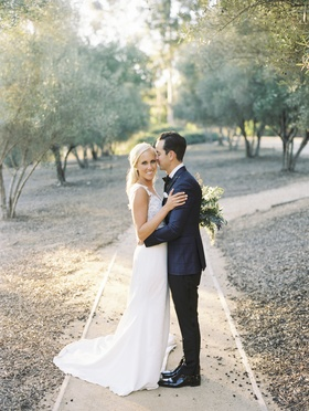 bride in pronovias wedding dress, groom in blue windowpane suit jacket pathway among trees