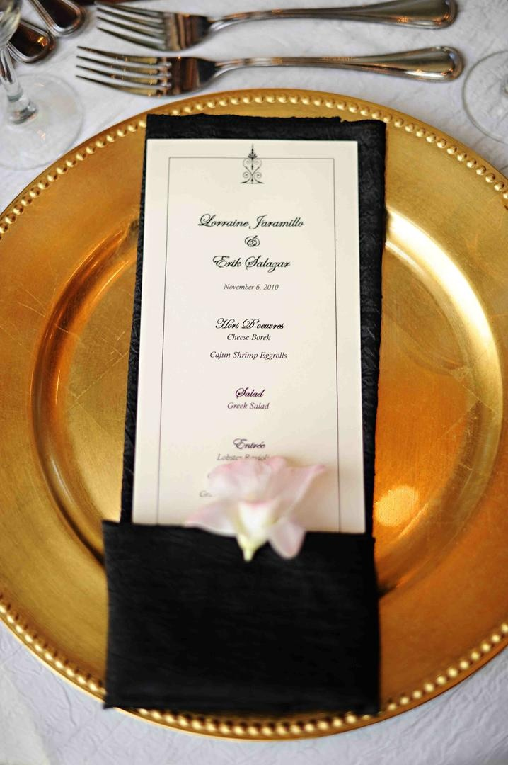 Black and white menu card in napkin on gold plate