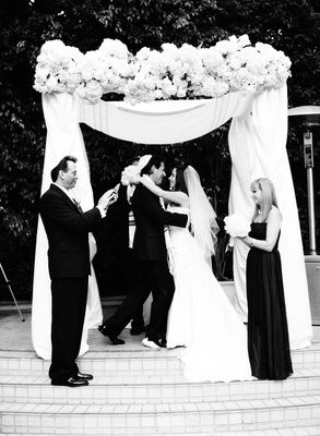 Black and white photo of bride and groom embracing at outdoor Jewish ceremony