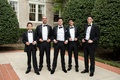 groom, groomsmen, young groomsmen in classic black tuxedos tug on suspenders