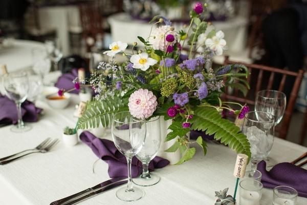 Wedding reception Lyndsy Fonseca and Noah Bean ferns purple flowers purple napkin wood chair