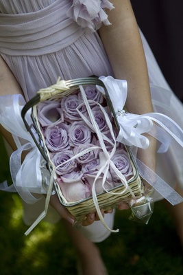 Flower girl holds wicker basket filled with purple roses