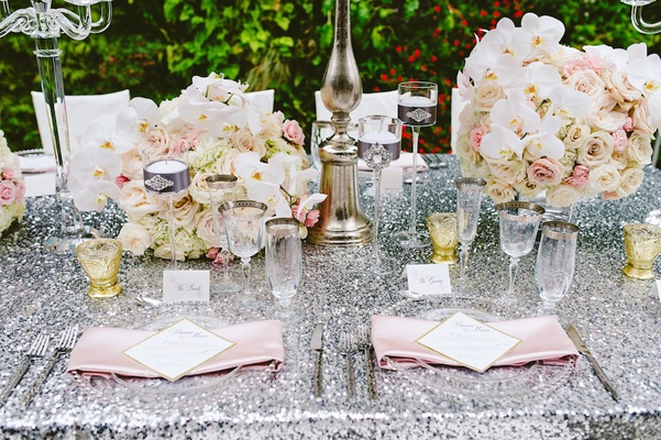 Rooftop garden wedding reception table with sequin tablecloth, pink napkins, wine glasses with gold