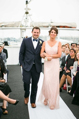 groom in navy joseph abboud suit escorted by mother in blush gown on yacht wedding