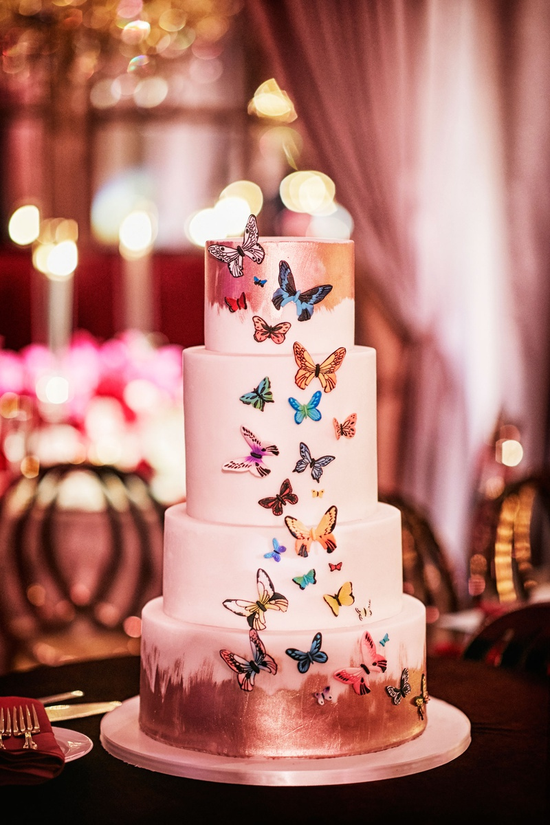 four layer wedding cake with brushstroke accents and colorful butterfly design applique