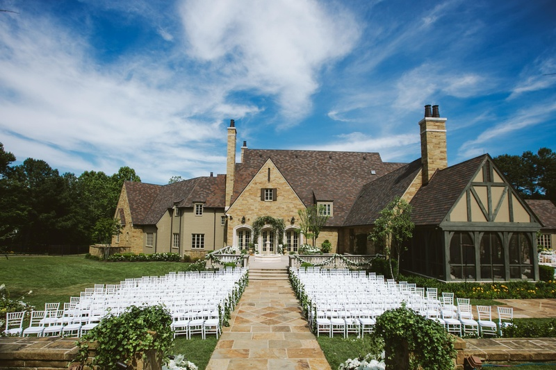 Outdoor wedding with white chairs and garlands