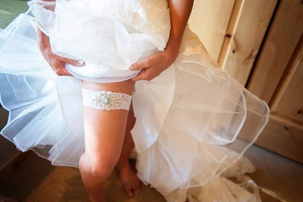 Bride pulling up wedding dress to show white leg garter with jewels and blue stone