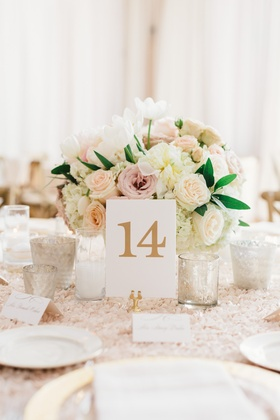 Low flower arrangement of pink and white roses white tulip flowers textured linen gold table number
