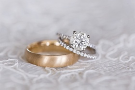 Groom's brushed yellow gold wedding ring, bride's diamond wedding band and diamond engagement ring