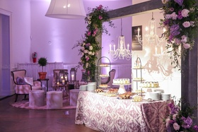 Beautiful floral adorns an arch above a lavendar accented sweet table.