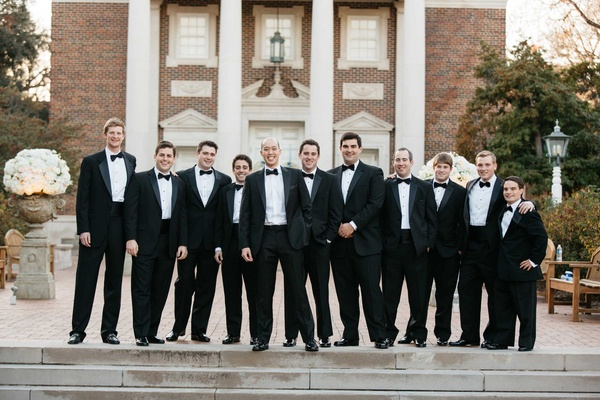 Groom and groomsmen in front of Perkins Chapel in tuxedos with bow ties