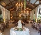 Barn wedding reception with elegant design white drapery linens naked cake chandelier greenery