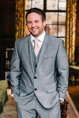 groom poses indoors in a gray tuxedo with a champagne colored tie