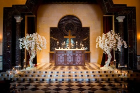 wedding altar at Grand Del Mar chapel framed by tree arrangements wrapped in orchid flowers