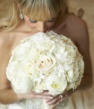 Bride with bangs smelling ivory flowers