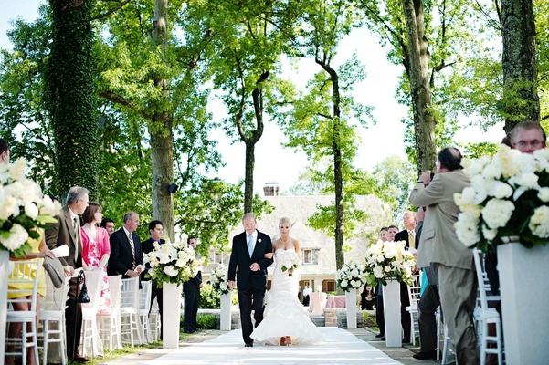 Bride walks down aisle with father under green trees