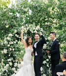 Jillian Murray and Dean Geyer celebrating their wedding day after ceremony flower arch trees
