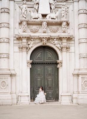 Bride in Hayley Paige wedding dress in front of historic building door columns carvings sculpture
