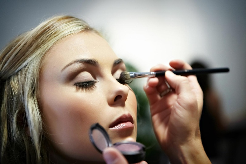 Bride having makeup artist put on eyeshadow for wedding