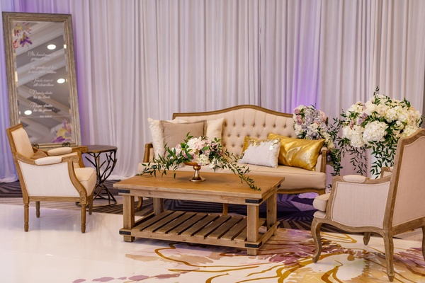 Wedding reception wood coffee table tufted settee armchair flowers gold pillows drapery custom floor