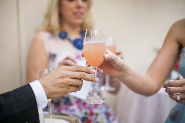 Bride to be passing glass of peach Bellini to bridal shower guest
