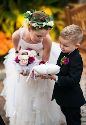Flower girl in ruffle skirt with basket pink flowers and flower crown greenery helping ring bearer