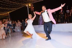 bride in mark zunino high-low wedding dress groom in salmon tuxedo jacket, choreographed first dance