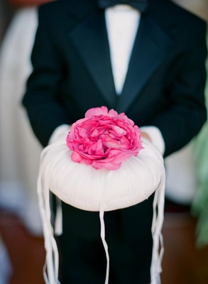 Ring bearer holding circular pillow with flower