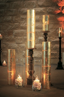 Pillar candles in glass vase with flowers