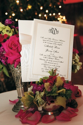 White invitation with black lettering and tan border and ribbon