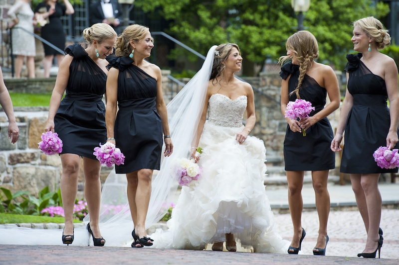 Bridesmaids in one-shoulder Lynn Lugo black dresses, bride in strapless Lazaro gown, peony bouquets