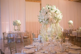 Wedding reception round table with tall centerpiece white flowers and cascading flowers to table